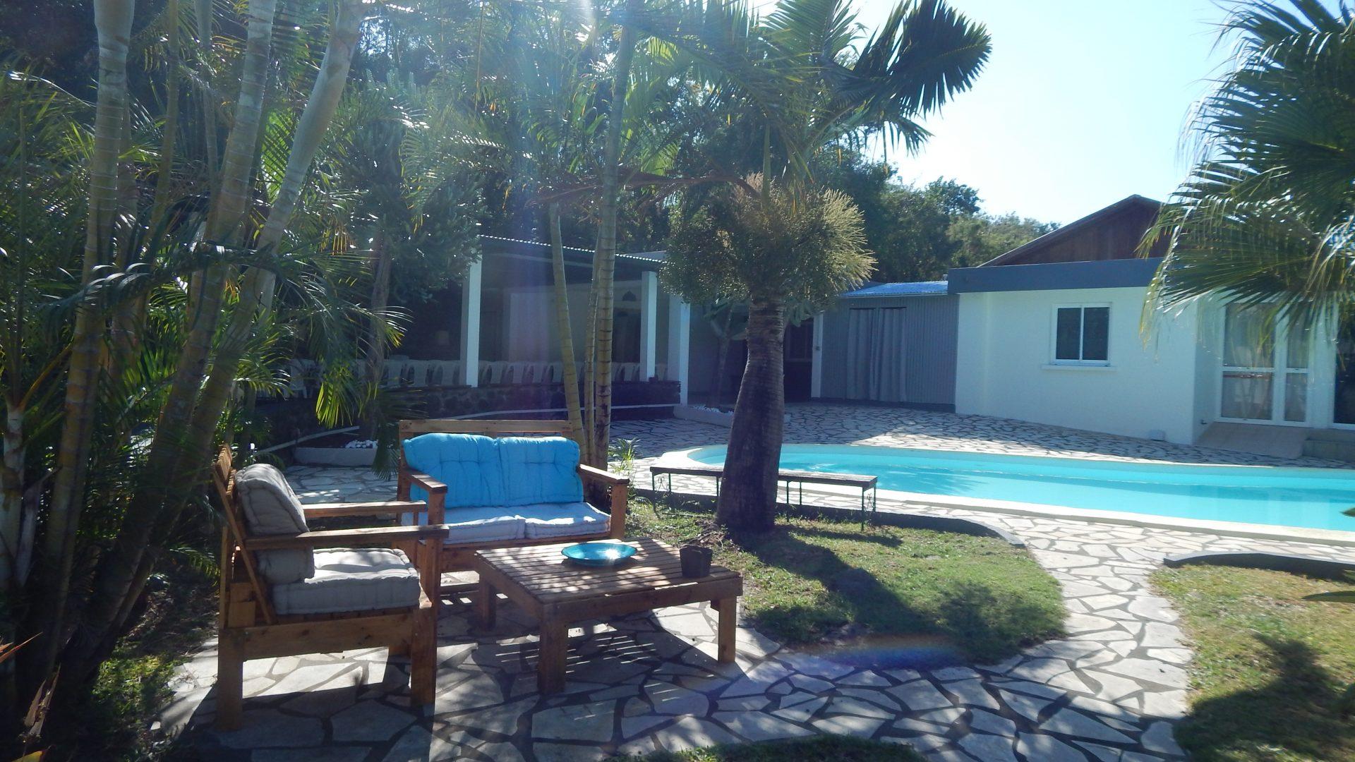 Salon de jardin à l'ombre et vue sur piscine